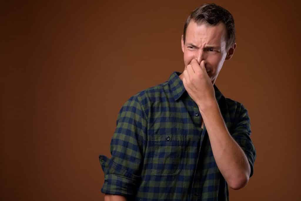 גבר בחוולצה משובצת תופס את האף בגלל ריח מסריח